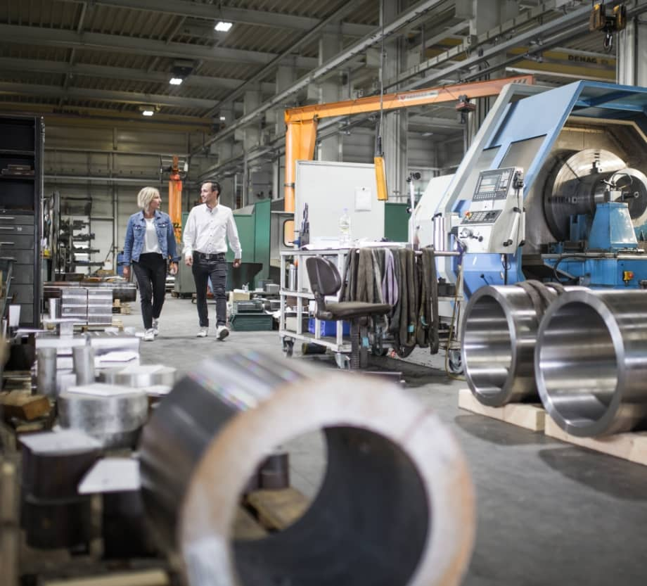 Mann und Frau laufen durch Produktionshalle
